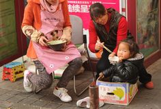 A woman using disposable wooden chopsticks to feed a young girl on a street in Shanghai. China Food, Chopsticks, Addiction, Forests, Shanghai, Utensils, Environment, Trees, Friday