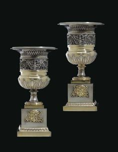 A PAIR OF ITALIAN PARCEL-GILT SILVER URNS ON STANDS