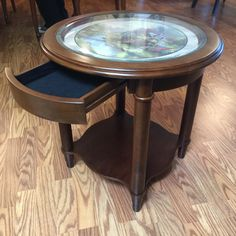 THOMAS KINKADE OCCASIONAL TABLE WITH BEVELED GLASS TOP OVER A COTTAGE SCENE. IT HAS ONE DRAWER AND A LOWER SHELF. COORDINATES WELL WITH THE KINKADE LAMP IN LOT 10024. 22H X 22W