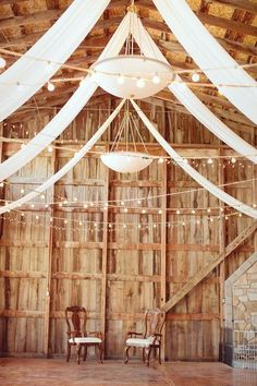 Rustic wedding reception decor idea - draped white fabric and string lights {Creatively Yours} For more wedding inspiration check out our wedding blog www.creativeweddingco.com