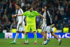 Goalkeeper Iker Casillas of Real Madrid CF holds teammates Isco and Sami Khedira in order to greet the audience close to Raphael Varane after loosing the UEFA Champions League round of 16 second leg match between Real Madrid CF and FC Schalke 04 at Estadio Santiago Bernabeu on March 10, 2015 in Madrid, Spain.