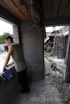 ウクライナ東部ドネツク(Donetsk)近郊のMaryinka村で、前日の政府軍の砲撃によって破壊された自宅の中に立つ男性(2014年7月13日撮影)。(c)AFP/DOMINIQUE FAGET ▼14Jul2014AFP|ウクライナ東部で戦闘激化、民間人15人死亡 http://www.afpbb.com/articles/-/3020428