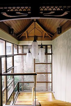 The glass windows open up the staircase landing. Recycled teak wood makes up the stairs and the railings are made of rattan strips. Capiz lamps hang from the ceiling add a traditional Filipino touch. Modern Filipino Interior, Asian Interior, Tropical Interior, Filipino Architecture, Tropical Architecture, Filipino House, Bali, Zen Interiors, Staircase Landing