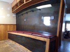 Mud room bench with 6 individual compartments for boots, patina'd steel by feet and wall with coat hooks and rods for hanging coveralls and upper cabinents for hats and gloves