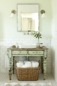 Oh my, the old chippy desk works perfectly for a bathroom sink, I especially love the big basket full of white rolled towels