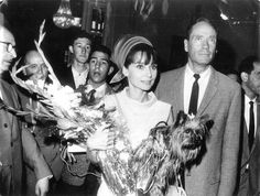 The actress Audrey Hepburn (with Assam of Assam) photographed with her husband Mel Ferrer during their arrival for a projection during the XII International Film Festival San Sebastián in San Sebastián (Spain), on June 05, 1964. Audrey was wearing: Ensemble: Givenchy (of silk linen, sleeveless blouse and skirt, of his collection for the Spring/Summer of 1963). Turban hat: Givenchy (created especially for her). Handbag: Cartier Ltd. London.