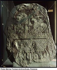 Carved funerary stone. A hero possibly Odin riding the eight-legged horse Sleipnir is welcomed to Valhalla by a Valkyrie holding a horn. Valhalla is depicted at the left as a round-topped building.