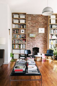 A modern living space with exposed brick wall, black chairs, coffee table full of magazine, and a built-in bookshelf