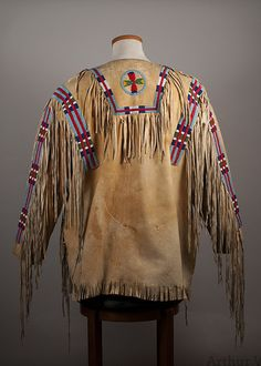 """Size: L. 33"""" A large Plateau man's fringed buckskin shirt with beaded strips and beaded medallion at the neck. The shirt is very traditional with open sides withjust buckskin ties, It shows wear at th"""