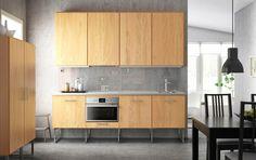 A modern line kitchen with HYTTAN oak veneer fronts, white HÄLLESTAD worktops and METRIK handles in stainless steel