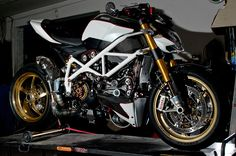 Modded White Ducati Streetfighter with a white trellis frame, OZ rims and a D&D exhaust