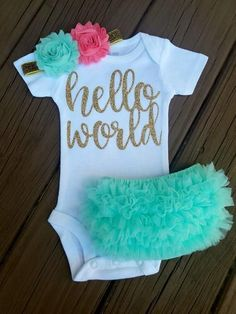 Dress your little princess up in this super cute mint, gold and rose coral Newborn take home outfit. Perfect for taking your new baby girl home from the hospital, her first photo session or an awesome baby shower gift! This listing includes flower headband, bodysuit and ruffle butt bloomers. Bodysuit is adorned with gold glitter lettering which is super sparkly and shed free and reads Hello World. Bodysuit is available in short or long sleeve. Please make your selection at checkout.  Ca...