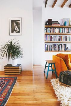 Wooden floors and white walls like ours but strong coloured armchair