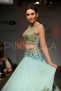 Karisma Kapoor walked the ramp to showcase designer Arpita Mehta's collection titled 'Paradiso' at the Lakme Fashion Week 2014. The collection was stirred by the designer's holiday in the island of Mykonos. Karisma wore an intricately embroidered ice blue crop choli with mirrorwork and 3D mirror flowers, teamed with a flowy ice blue silk chiffon skirt with mirror-work at the hem and waistband.