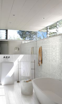 White timber-look floor tiles in bathroom; freestanding bath, pedestal basin and towel rack; high louvre windows