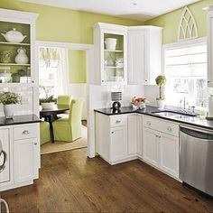Green walls, white kitchen cabinets, Dark counters, stainless appliances.