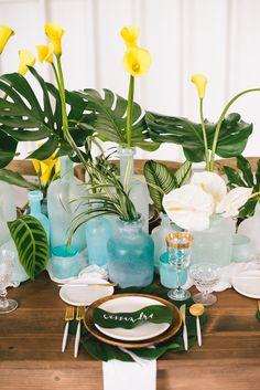 aqua sea glass centerpieces - photo by Krista Mason Photography http://ruffledblog.com/tropical-leaves-and-sea-glass-wedding-shoot