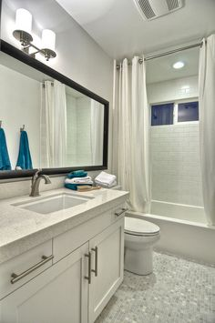narrow bathroom layout with windowed bathtub along width and vanity and toilet along long wall