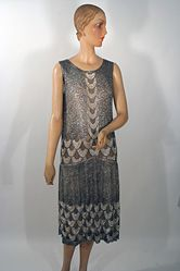 1925 French Beaded Flapper Dress made in France by Frenchshire, this understated (by 1920s standards) flapper dress is entirely covered with silver beads and gelatin sequins on a net base. The only areas that are not covered are the centers of the fish scale scallops at the waist and hem lines and center front.