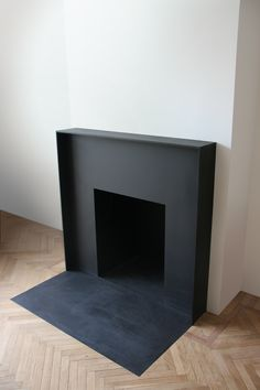 Black minimalist fireplace stands out against pale herringbone parquet flooring