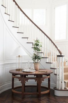 Elegant foyer features a curved staircase wall clad in wainscoting lined with a round table topped with a Ralph Lauren Home Modern Accent Lamps atop a wood herringbone floor.