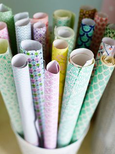 Repurpose clean wastebaskets or laundry bins as an attractive way to contain wrapping paper or spooled fabrics.