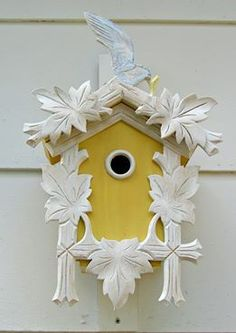 Bright yellow birdhouse. Trim is made from pieces of antique cross frames. Beautiful!