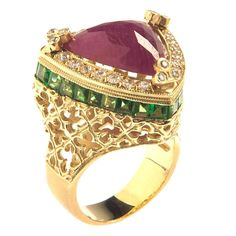 18K Gold Ring with Sliced Ruby center surrounded by diamonds.  On edge of ring are princess-cut Tsavorite.  Center Ruby, 10.86ct.