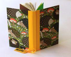 Erizos en el jardín -  Cuaderno MOW, 100 hojas, papel reciclado, tapa forrada en papel, lomo vinilo amarillo, hoja de guarda delantera color verde y trasera color café. Cinta separadora de páginas, color amarillo.