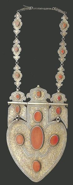 Extremely large ornament of silver set with large carnelians. All over ornamentation of lozenges of gilt silver. The tire track style framing is a style that is found only on these Yomud ornaments from Khorezm.  sold by Singkiang 2006