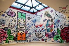 A stenciled graffiti installation by Lady Aiko, a Japanese-born street artist who currently resides in Brooklyn. The mural breathes life into the sterile gallery with an image centered around a woman with a back tattoo sitting in the shadow of a wave.