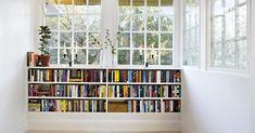 Inbyggd bokhylla under fönster.