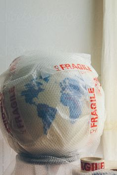 Globe covered in bubble wrap and Fragile tape. by kkgas | Stocksy United