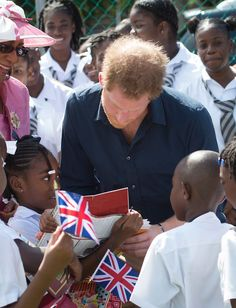 Prince Harry Photos Photos - Akia Slocombe shows Prince Harry a picture of her father Tim who was injured while serving in Afghanistan during his visit to a community sports event on the ninth day of an official visit to the Caribbean on November 28, 2016 in St Geoorges, Grenada. Prince Harry's visit to The Caribbean marks the 35th Anniversary of Independence in Antigua and Barbuda and the 50th Anniversary of Independence in Barbados and Guyana. - Prince Harry Visits The Caribbean - Day 9