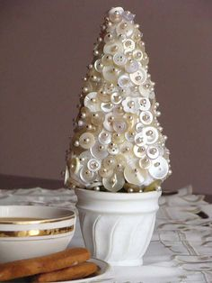 Oh, I love this button tree! So elegant. Looks like pearl-top pins pushed into button holes and attached to a styrofoam cone. Blue on the pins to make them stick? Won't know until I try it. Image found on flickr: http://www.flickr.com/photos/26386899@N04/3170300886/in/faves-14242866@N05/