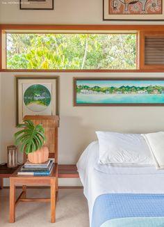 Cadeira de madeira usada como criado mudo nesse quarto de casal em Ilhabela.