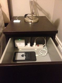 Power strip in bedside table for tidy multi-device charging.