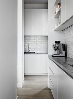 Butler's pantry / small kitchen: white handmade subway tile splashback, grey marbled stone benchtops, matt white handleless cabinets, open shelving, pale timber floorboards