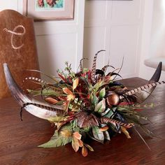 "Decorate your table, mantle or shelf with a handmade original art piece as free-spirited as the West itself. The design combines a pair of real cow horns filled with dried flowers, pods and natural feathers that provide lasting beauty. Please allow 2-4 weeks for delivery. 37""w x 10""h."