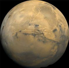 Valles Marineris, Mars  This image, a collaged mosaic of 102 photographs taken by the Viking 1 Orbiter in 1980, shows Mars and the vast Valles Marineris that cut a deep gash through the planet's equator. The system of canyons is 4,000 kilometres in length, 200 kilometres wide, 8 kilometres deep at its lowest points, and as such is the biggest known canyon in the solar system.
