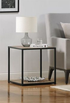 Compact and slender, the Ameriwood Home Canton Accent Table with Metal Frame is a great addition to your living room or bedroom. Set it next to the couch to hold your remotes, table lamp and reading materials. Featuring a sturdy top and roomy bottom shelf, the sleek design blends industrial and modern styles together. Finished in a metal gray on all 4 sides, this light brown oak laminated particleboard and painted metal table measures 20.86