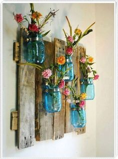 Great wooden vertical garden --> turn several mason jars into flower vases, hang on the pallet add flowers or green hanging plantings | Other pallet decor ideas on this blog
