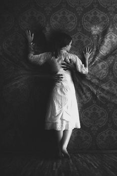 Black and white photograph centered on a woman who apparently longs for companionship. The walls reach out to hold and comfort her; implying a bond both household and human must share through a loss. The wall doesn't just stretch out; the mass forms human hands that hug the woman like a lover.