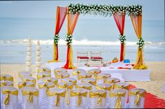 Beach Wedding Inspirations - Yellow and Red Drapes for Mandap along with White Roses, and White with Gold Seating Arrangement | Perfect Wedding in Goa | WedMeGood #wedmegood #beach #weddings