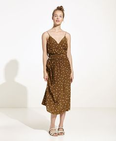 Polka dot midi dress, 29.99€ - Midi dress with a polka dot print over a brown base, slit in the front up to the waist and belt fastening. Garment measurements: Total length from point of union between neckline and shoulder: 110.5 cm, chest width: 29 cm and hip width: 42 cm. These measurements are calculated based on a Spanish size M. - Find more trends in women fashion at Oysho .
