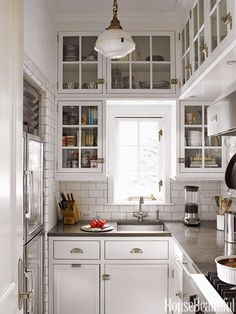 small kitchen, school house light fixture, cabinet latches, white cabinet, gray, cement counter tops, white subway tile with dark grout, small fridge option