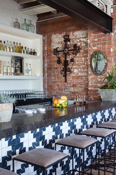 Mexican tile bar, exposed brick, simple stools, plain white bar shelves allow the bottles to be the color, open metal beam, traditional wrought iron sculpture