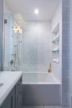 Behind a glass partition, a drop in tub is positioned beneath tiled niche shelves framed by marble subway tiles and facing a vintage hand held shower head as mosaic marble tiles accent an adjacent wall.