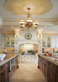 Giving a kitchen its own personality requires careful consideration focused on decorating, and adding the right finishes and details.  Beautiful double island antiqued white kitchen with acanthus corbels, beautiful ceiling design, fabulous lighting fixtures.   #ceiling   #ceilingdecor   #kitchen   #kitchendesign