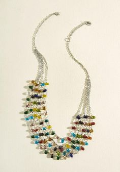 Accelerate the allure of any ensemble with this colorful statement necklace!  Revved up with shining silver chains and an array of prismatic glass beads,  ...